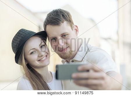 Touristic couple shooting on the modile phone selfy at the city streets under sunlight.