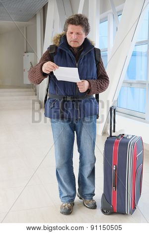 Male tourist standing with travel suitcase