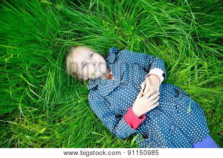 Little Blonde Girl Lying On The Grass And Dreaming