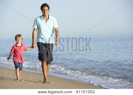 Father And Son Enjoying Walk Along Beach