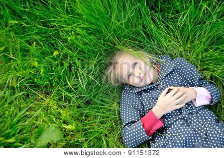 Happy Little Girl Dreaming On  The Grass And Enjoying Summer