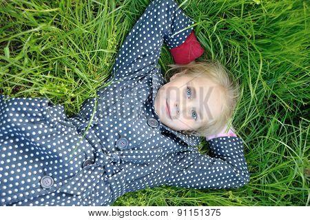 Portrait Of Little Girl Lying On Green Grass