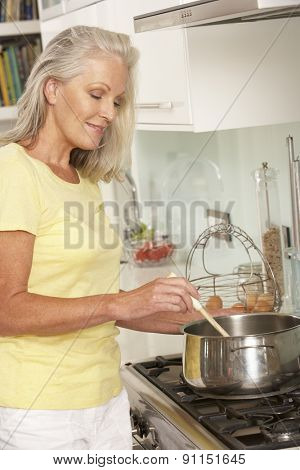Senior Woman Preparing Meal At Cooker