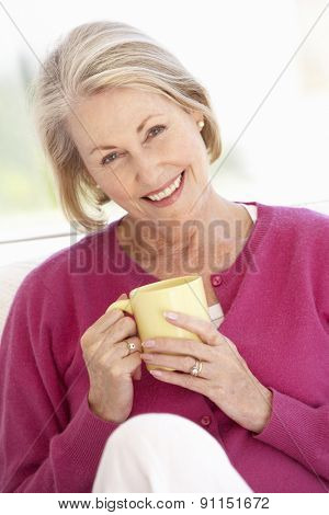 Senior Woman Relaxing At Home With Hot Drink