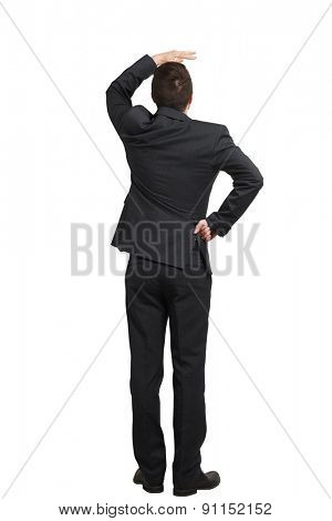 back view of businessman in black suit looking up and covering one hand over white background