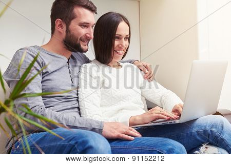 indoor photo of young adult couple sitting on sofa and using laptop
