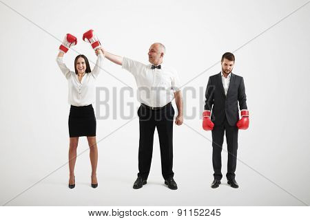 referee holding happy winner businesswoman in boxer gloves and looking at her, near standing sad loser businessman over light grey background