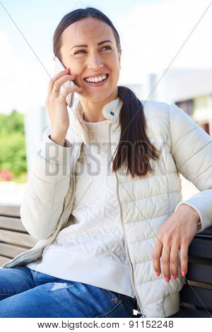outside photo of smiley young adult woman talking on the cellphone