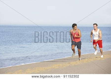 Two Young Men Jogging Along Beach