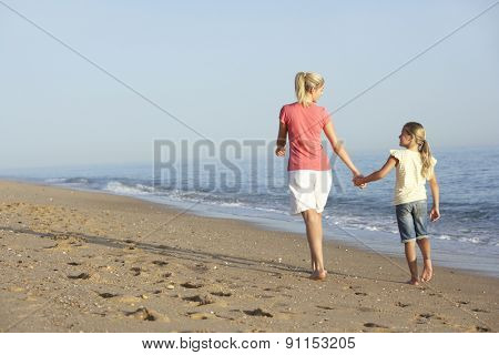 Mother And Daughter Enjoying Walk Along Beach