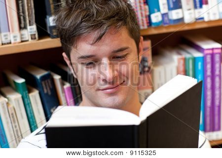 Portrait Of A Smiling Male Student Reading A Book Sitting On The Floor
