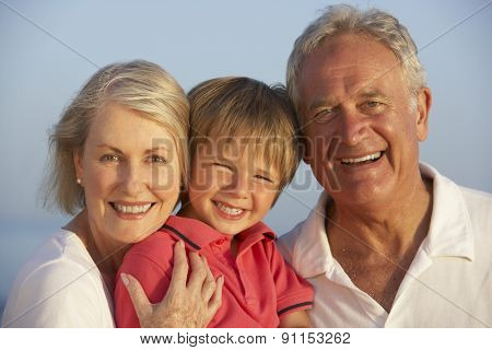 Grandparents With Grandson Enjoying Beach Holiday