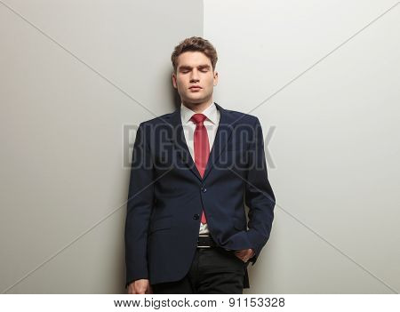 Handsome business man leaning on a wall with his eyes closed hinking.