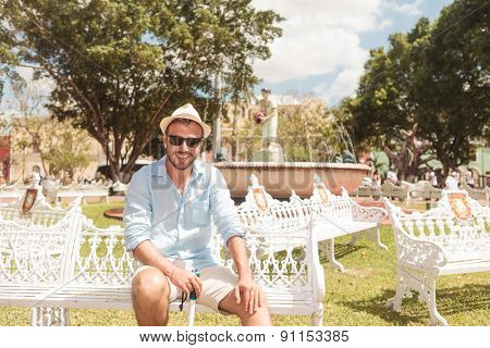 Smiling young man sitting on a white bench, looking at the camera.