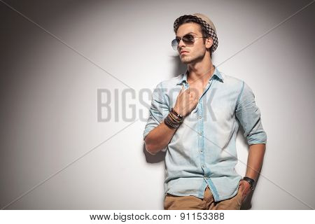 Attractive fashion man looking away while pulling his shirt.
