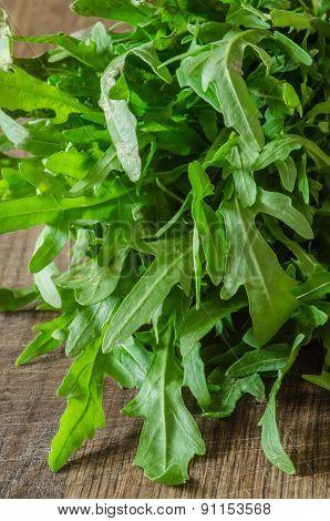 Ripe organic arugula on wooden background closeup