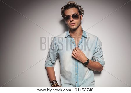 Young casual fashion man looking at the camera while fixing his shirt.