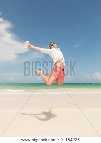 Happy young man jumping on the beach, celebrating freedom.