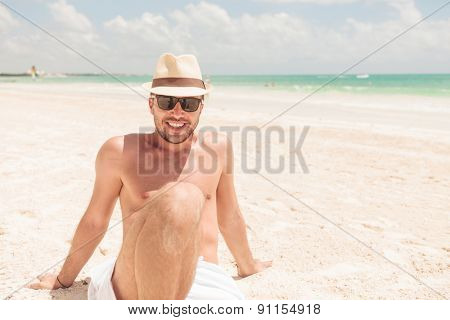 Happy man enjoying his vacation. He is sitting on the beach leaning on his hands.