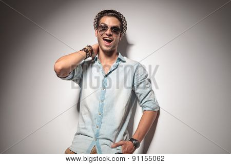 Happy young fashion man smiling to the camera while holding one hand in his pocket.