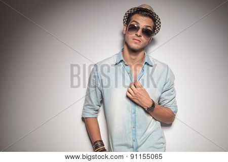 Casual young fashion man leaning on a grey wall while fixing his shirt.