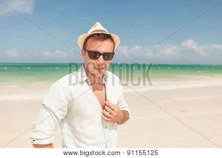 Attractive young man posing on the beach while fixing his shirt.