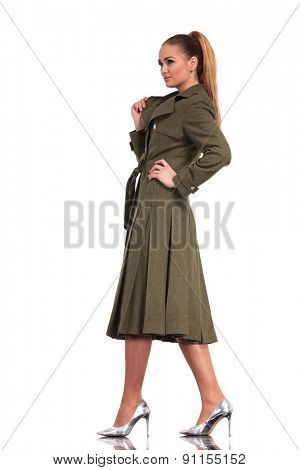 Gorgeous young business woman walking on studio background in a elegant long coat.