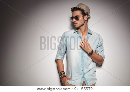 Handsome young casual man looking to his side while holding one hand in his pocket.