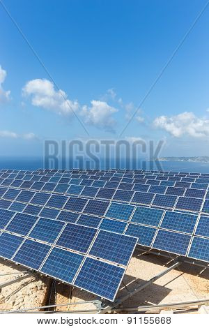 Group of solar collectors near blue sea