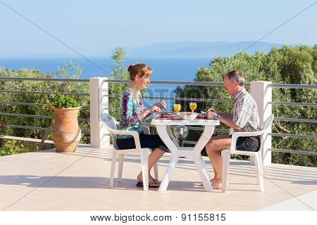 Man and woman eating at table on terrace near sea