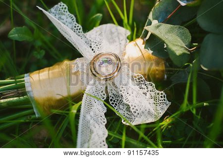 Two Wedding Rings On Bridal Bouquet Of Flowers