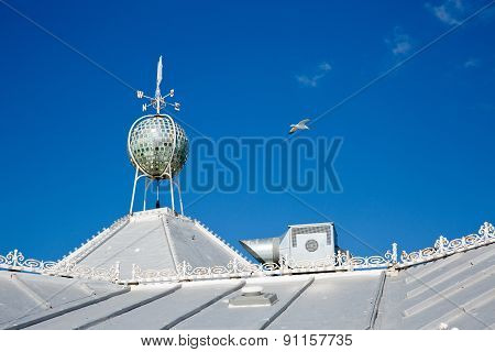 A White Cladded Roof With A Wind Indicator On The Roof On A Sunny Day