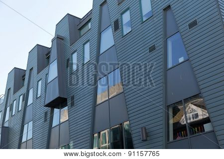 An Image Of A Grey Metal Cladded Facade With Angled Lines Dividing The Material