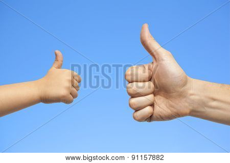 Father And Son Hands Giving Like On Sky Background