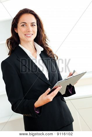 Glowing Young Businesswoman Taking Notes On Her Clipboard