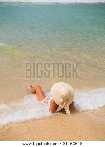Summer vacation woman on the beach in beach hat enjoying summer holidays looking at the ocean