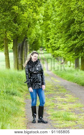 woman wearing rubber boots in spring alley