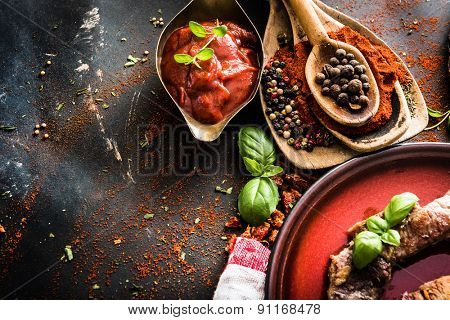 grilled meat on a plate with tomato sauce, spices on textured black background