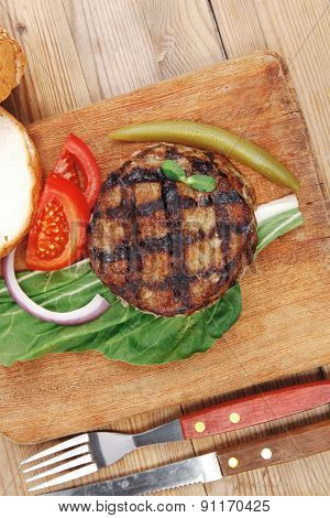 extra thick hot beef meat hamburger lunch on wooden plate with tomatoes and salad over wooden  table with cutlery and fresh sweet bun