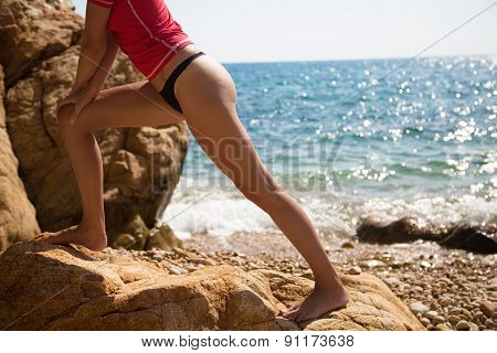 Sexy Girl In Sportswear And Tanga String Training On The Cliff Of The Rocky Beach .