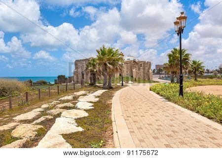 Pedestrian walkway, lampposts and ancient on promenade along Mediterranean sea coastline in Ashqelon, Israel.