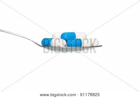 Blue White Medicine Or Capsule On Spoon Isolated On White Background