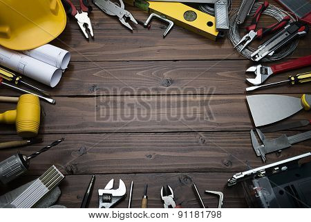 Construction equipments on brown wood background with copy space.  Blueprints are not subject to copyright. Words on them are regular like kitchen, bedroom, bathroom etc.