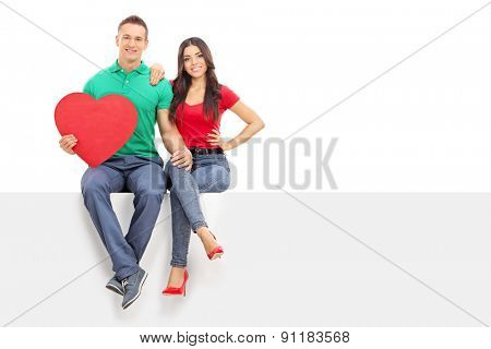 Young handsome man holding a big red heart seated on a blank billboard with his girlfriend isolated on white background