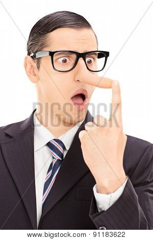 Vertical shot of a young displeased businessman looking at his long nose and trying to put it back with his finger isolated on white background