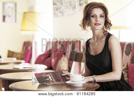 Young girl drinking coffee during the job break