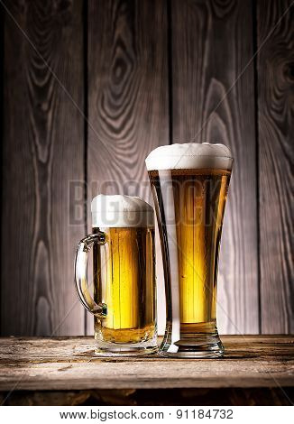 Tall glass and mug of light beer with foam