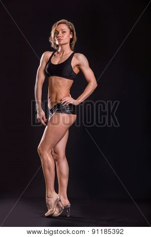 Sexy athletic blonde posing on a black background.