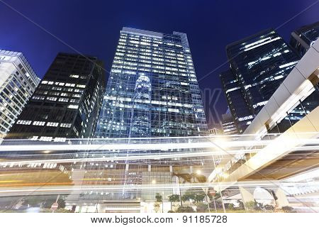 Office buildings at night with traffic trails