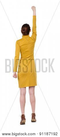 Back view of  woman. .  Isolated over white background. Girl in  dress standing in a pose superhero. Girl in mustard strict dress raised his right hand with the palm clutched in his fist.